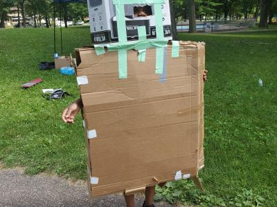 young kid in a cardboard robot costume.